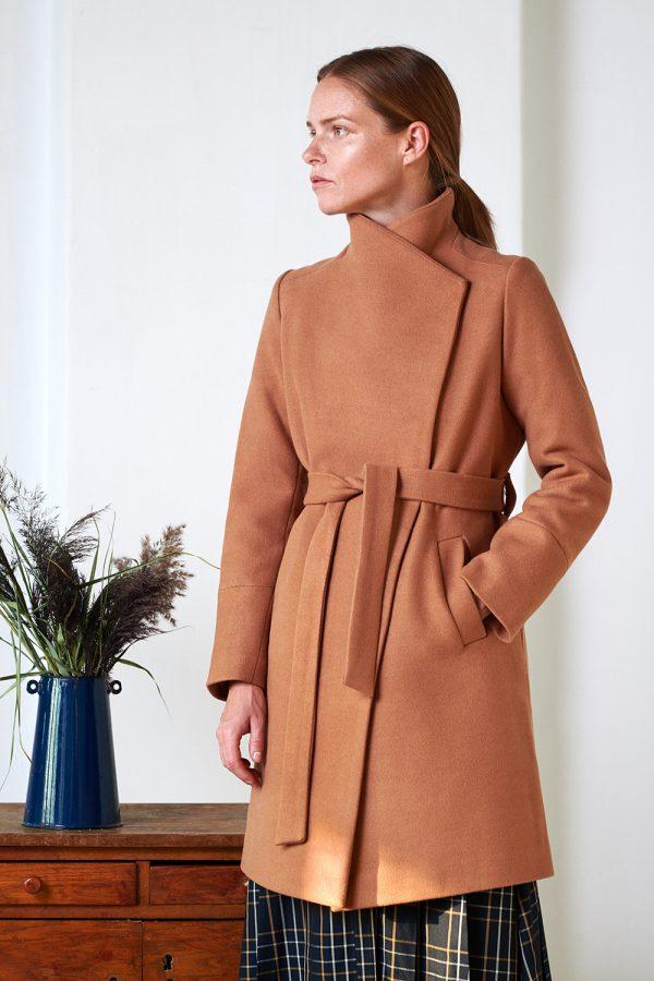 kamelowy płaszcz damski wiązany w pasie z asymetrycznym przodem