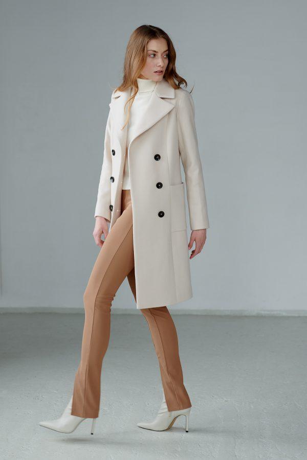 Wiosenny płaszcz dwurzędowy do kolana, z dużymi klapami, ozdobną patką z tyłu oraz naszywanymi kieszeniami.