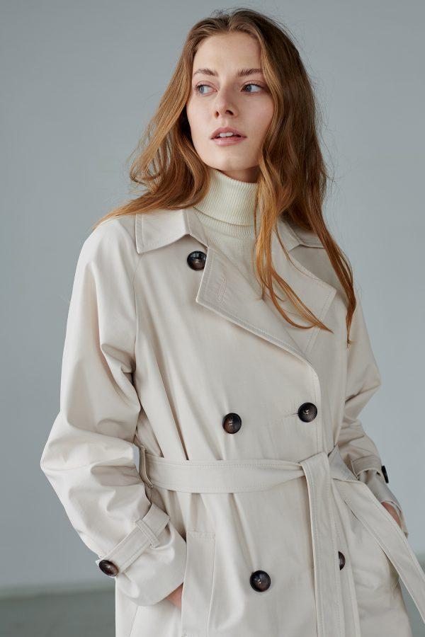 Długi płaszcz trenczowy z peleryną na tyle, obszerny, oversizowy, wiązany i zapinany na guziki.