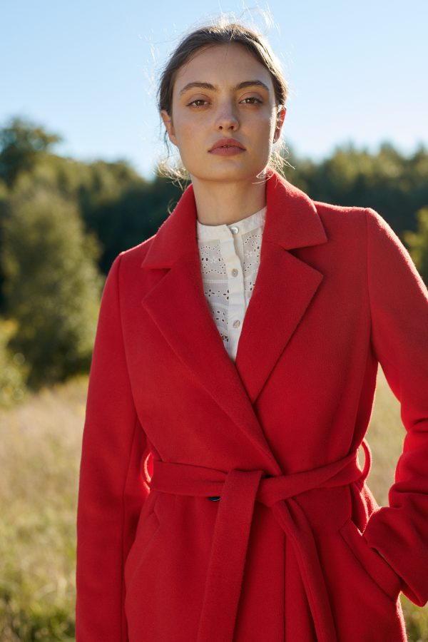 czerwony damski płaszcz z wykładanym kołnierzem typu rewers wiązany w pasie